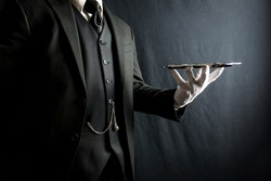 Portrait of Butler or Waiter in Dark Suit and White Gloves Holding Silver Tray on Black Background. Concept of Service Industry and Professional Hospitality.