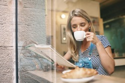 Portrait of cafe city lifestyle woman sitting in trendy urban cafe reading magazine and drinking coffee with a croissant during your vacation