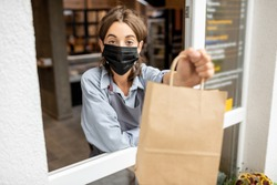 Portrait of cafe or small shop female worker in protective mask looking out of the window with food to take away. Concept of a business work during a pandemic