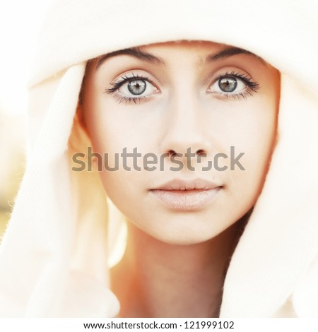 Portrait of calm beautiful young woman in head scarf close up against bright sunlight