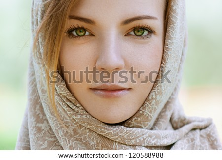 Portrait of calm beautiful young woman in head scarf close up, against green of summer park.