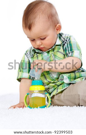 Portrait of calm boy with small bottle of drink near by