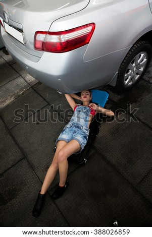 Portrait of car mechanic woman lying under car and solving problems. Beautiful lady in jeans working at repair shop.