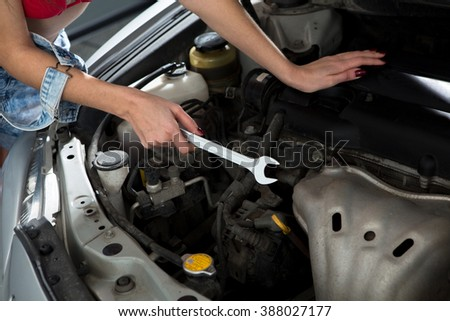 Portrait of car mechanic woman repairing electronic motor while holding wrench in front of her at repair shop.