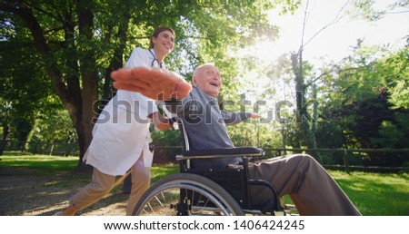 Portrait of carefree and happy young woman social worker or nurse  and senior man in a wheelchair having fun to run in a green park on a sunny day.