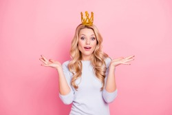 Portrait of carefree funky girl with gold crown on her head gesturing with palms looking at camera demonstrate her greatness isolated on pink background