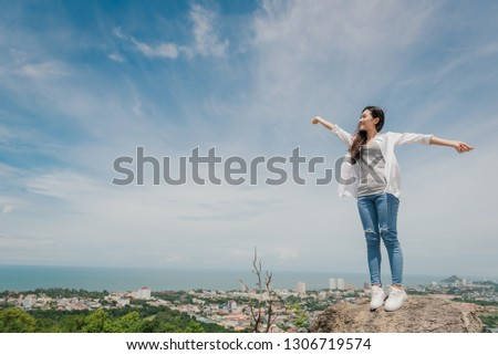 Portrait of carefree happy asian woman standing on top of mountain edge cliff enjoying  on her face. Freedom; Lifestyle; Enjoyment; Relaxing in mountains at Huahin in Thailand. #1306719574