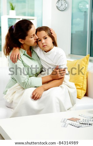 Portrait of careful female holds her sick daughter while both sitting on sofa