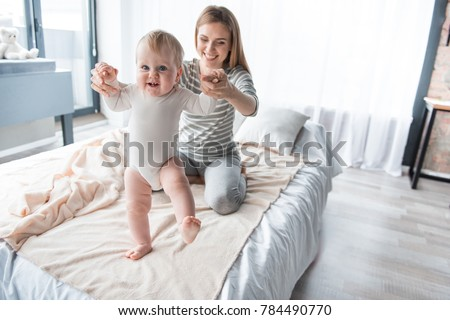 575ec1ab0b Portrait of caring mom sitting on bed and teaching her little kid walking.  Focus on