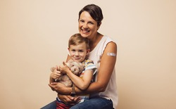 Portrait of carrying mother with her son after receiving a vaccine on arm. Mother and son with bandage on arm after getting immunity vaccine.