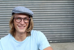 Portrait of casual blonde young man wearing glasses, news paperboy hat and blue crew neck t-shirt smiling and laughing with copy space