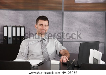 Portrait of casual businessman sitting at desk wearing short sleeved shirt, smiling. Copyspace on right.