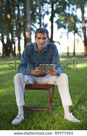 Portrait of casual middle aged man holding tablet PC
