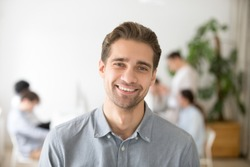 Portrait of casual smiling Caucasian male worker laughing looking at camera, positive employee posing for company business catalogue with colleagues at background, having photo shoot in office