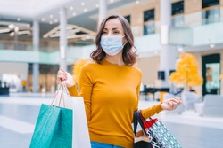 Portrait of casually dressed confident young woman wearing protecting medical mask while walking in mall with bunch of shopping bags in hands. Black friday sales concept.