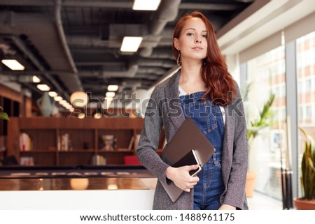 Portrait Of Casually Dressed Young Businesswoman Standing In Modern Open Plan Workplace