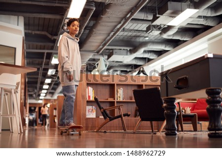 Portrait Of Casually Dressed Young Businesswoman With Skateboard Standing In Open Plan Workplace