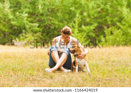 Portrait of cat and dog's interaction in their owner arms