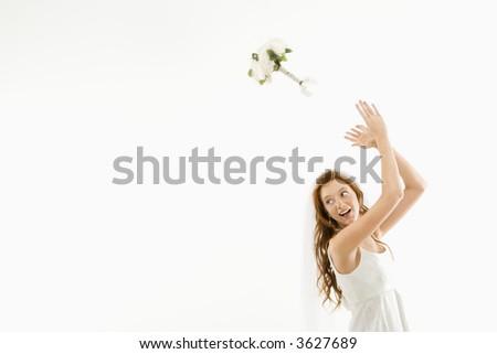 Portrait of Caucasian bride tossing bouquet behind her.