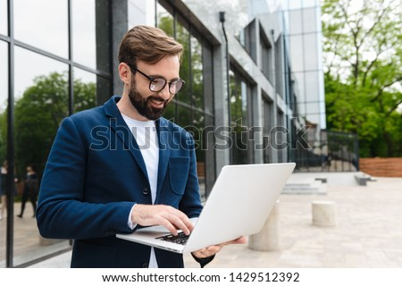 Portrait of caucasian businessman wearing eyeglasses using and looking at laptop while standing outdoors near building