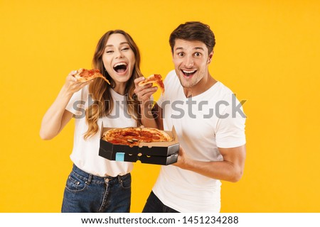 Portrait of caucasian couple man and woman in basic t-shirts smiling while eating pizza from box isolated over yellow background #1451234288