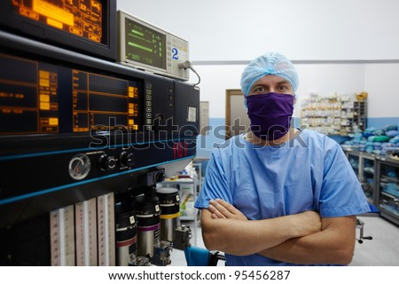 Portrait of caucasian doctor looking at camera in hospital surgery room with professional equipment and instruments