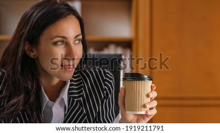 portrait of caucasian executive busineswoman being happy with smile sitting in office and holding coffee cup
