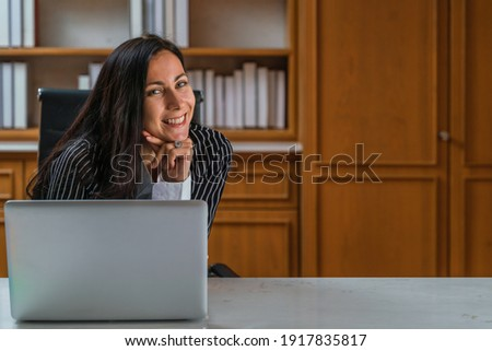 portrait of caucasian executive busineswoman being happy with smile sitting in office with laptop on desk