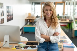 Portrait of Caucasian female graphic designer with arms crossed sitting at desk in a modern office. This is a casual creative start-up business office for a diverse team
