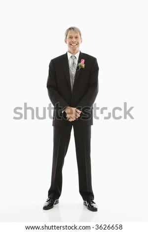 Portrait of Caucasian male in tuxedo with boutonniere.