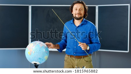 Portrait of Caucasian male teacher standing at board with pointer and pointing on globe in class. Man teaching geography in classroom. Online lesson. Lecturer explaining topic. Photo stock ©