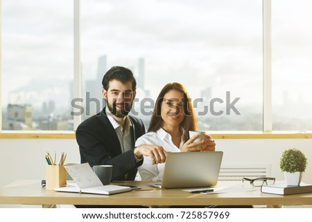 Portrait of caucasian man and woman working together at modern office desk. Meeting, teamwork, discussion and togetherness concept