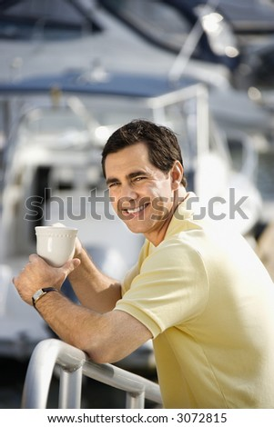 Portrait of Caucasian mid-adult male holding coffee cup at harbor looking at camera.