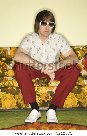 Portrait of Caucasian mid-adult man wearing sunglasses sitting on colorful retro sofa.