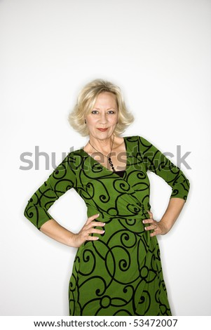 Portrait of Caucasian middle aged businesswoman standing with hands on hips. - stock photo