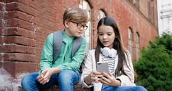 Portrait of Caucasian schoolkids sitting outdoor at schoolyard. Pretty teen girl typing and tapping on smartphone and talking to friend. Boy in glasses looking at cellphone screen. Classmates concept