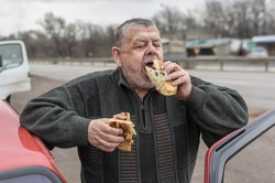 Portrait of Caucasian senior driver being delighted while gobbling lyulya kebab in lavash near his car