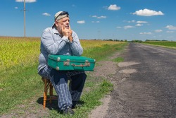 Portrait of Caucasian senior having short rest on a roadside sitting on a whicker stool with an ancient green suitcase