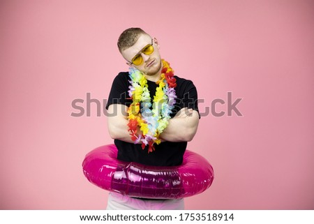 Portrait of caucasian stubborn resentful male with lei over neck and rubber ring. crossed arms and looks with displeasure from under forehead on pink background. Disagreement and stubbornness concept.