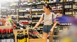 Portrait of caucasian woman buying at wine grocery store. Happy hispanic girl shopping in supermarket reading product information. Costumer buying alcoholic spirits at the market, woman lifestyle.