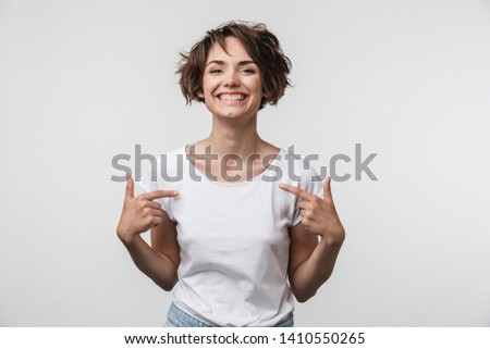 Portrait of caucasian woman with short brown hair in basic t-shirt rejoicing and pointing fingers at herself isolated over white background