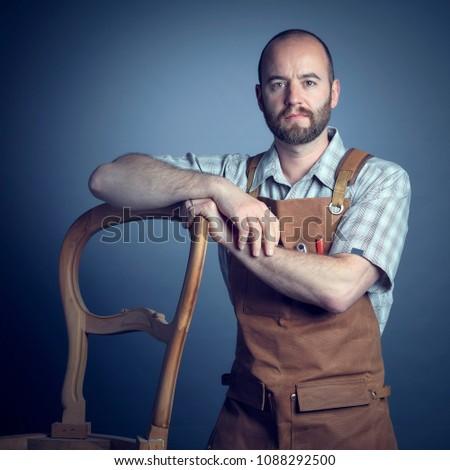 portrait of caucasian wood worker with apron studio shot