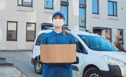 Portrait of Caucasian young female delivery postal worker in gloves and medical mask stepping in front of camera with parcel in hands. Close up of pretty happy woman handing carton box to cam outdoor.