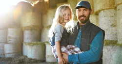 Portrait of Caucasian young handsome father holding on hands cute little daughter and smiling to camera at hay stocks in farm. Farming lifestyle. Countryside concept. Smiled man and small girl.