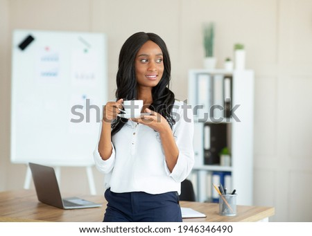 Portrait of charming black female manager in formal wear drinking coffee at contemporary office. Happy African American busineswoman taking break from work routine, enjoying hot drink