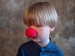 Portrait of charming blond boy in blue shirt with red clown nose and blue ball