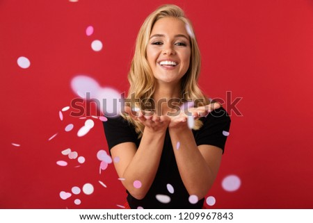 Portrait of charming blond woman 20s laughing and standing under falling confetti isolated over red background in studio #1209967843