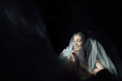 Portrait of charming bride enveloped in a veil. Beuatiful bride hidden under the veil. Beautiful bride in veil. Close up. Beauty woman. Wedding morning closeup on black background.