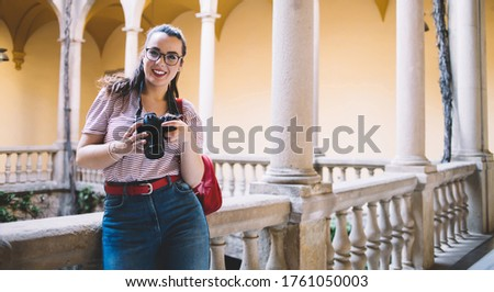 Photo of Portrait of charming caucasian woman in eyewear checking pictures on digital camera standing near architecture, smiling 20s female traveler enjoying free time on vacation using equipment for images
