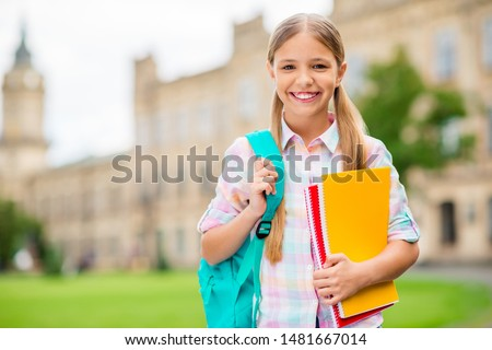 Portrait of charming child holding books smiling wearing checkered plaid t-shirt standing outdoors ストックフォト ©
